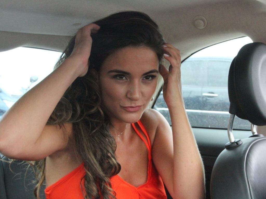 Laisa faz caras e bocas para os fotógrafos ao deixar o hotel no Rio de Janeiro rumo ao confinamento do