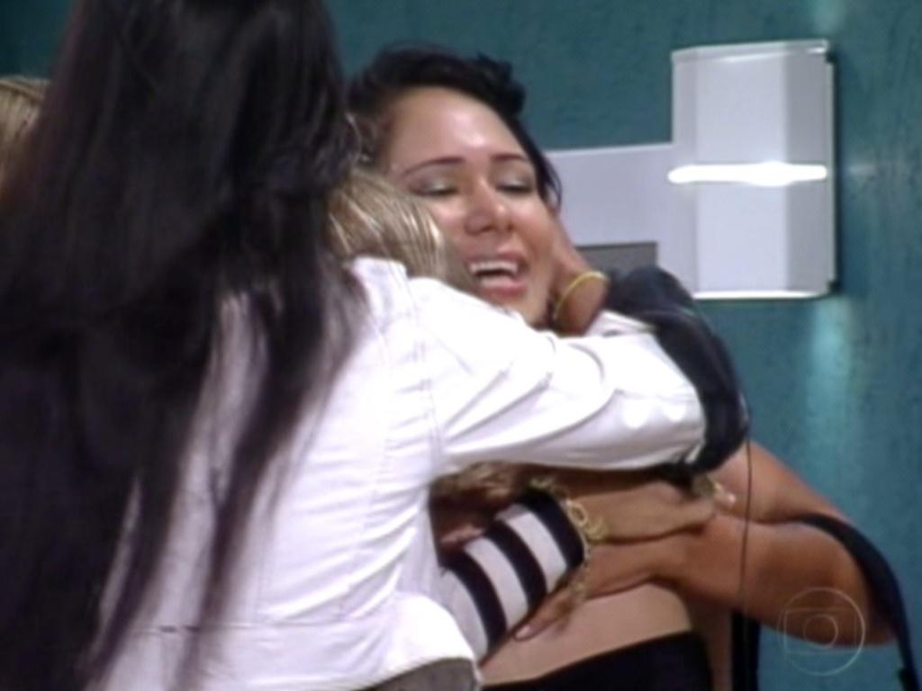 Jakeline (no centro) é abraçada por Kelly (de branco) e Renata (de preto) antes de deixar a casa do