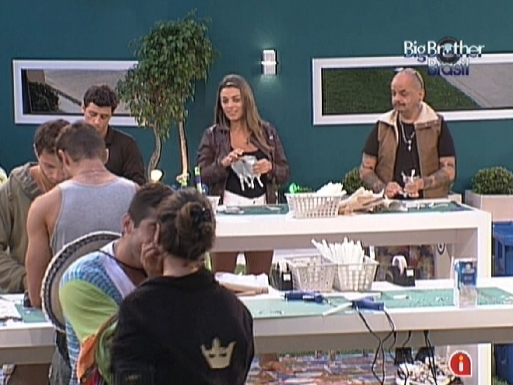 Monique (ao fundo) observa Laisa e Yuri se beijando durante prova da comida (28/1/12)