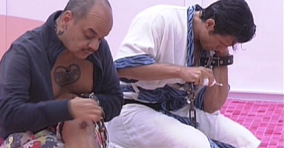 Acorrentados para pagar o castigo do monstro, João Carvalho (esq.) e João Maurício (dir.) fazem curativos em seus machucados (11/2/12)