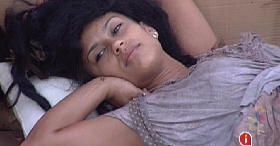 Vestida de mendiga, Kelly repousa na sobre caixas de papelão na área externa (25/2/12)