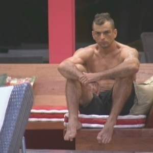 Pensativo, o lutador senta na beira da piscina