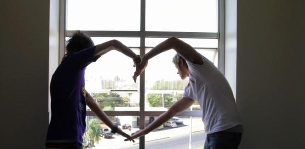Meninos do Restart fazem coração com os braço para fãs que os aguardam na entrada do hotel (12/11/10)