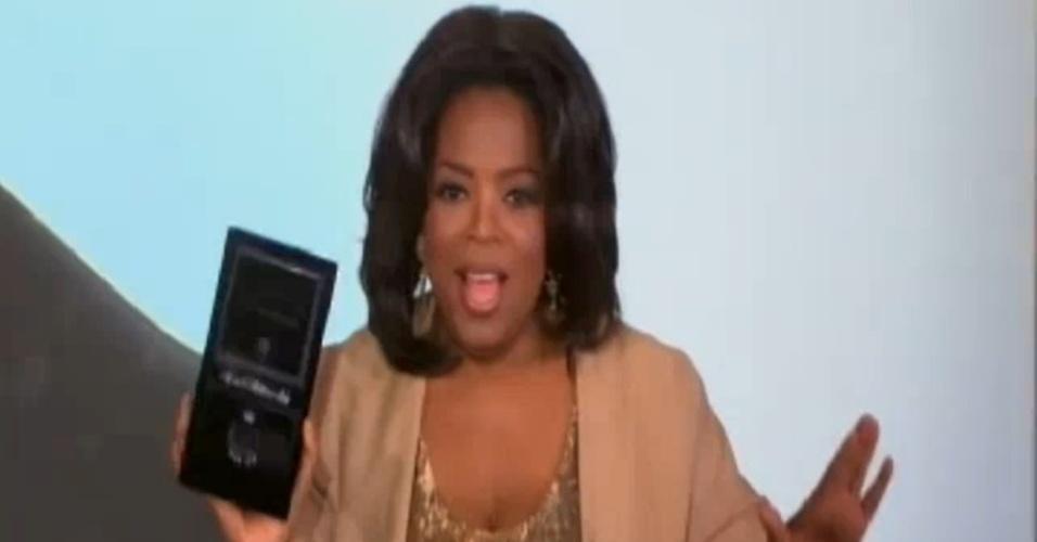 A apresentadora Oprah Winfrey segura uma das chaves dos carros dados de presente para sua plateia (24/11/2010)