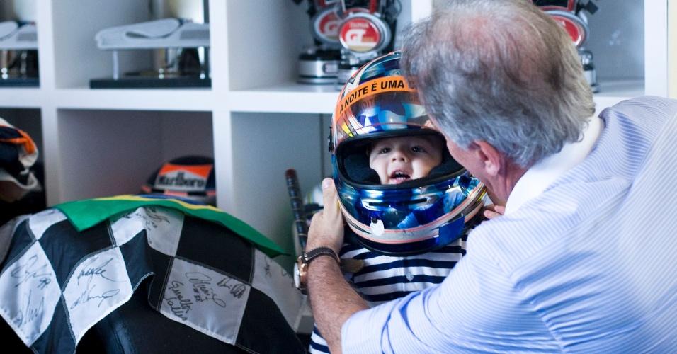 O apresentador Otávio Mesquita coloca um de seus capacetes na cabeça do filho Pietro, 2, que dá sinais de gostar de automobilismo também (12/5/2011)