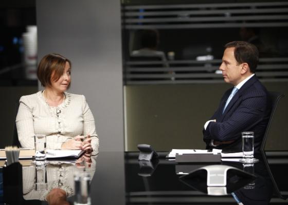 """Carla Pernambuco e João Dória Jr. conversam debatem durante sala de reunião em """"O Aprendiz 8"""" (2011)"""