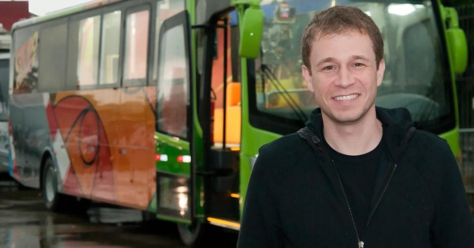 O apresentador Tiago Leifert posa em frente ao ônibus que será estúdio móvel do