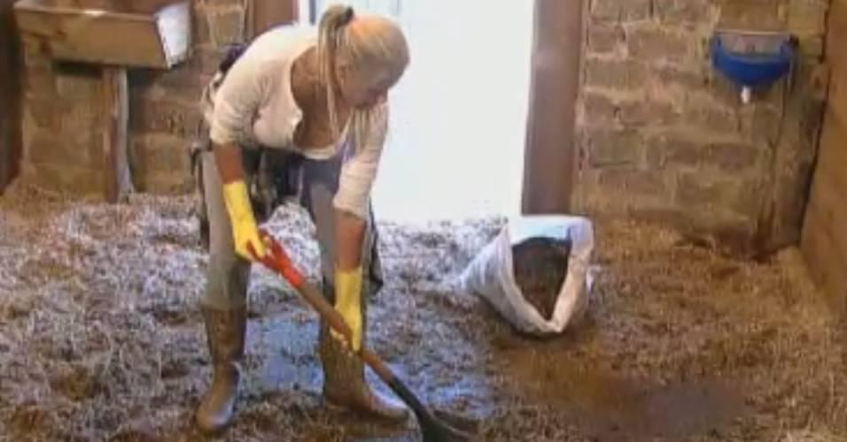 Monique Evans limpa a baia dos cavalos (18/8/11)